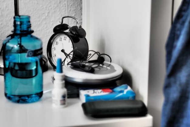 Wide angle shot of a clock, bottle and other objects on a table Free Photo