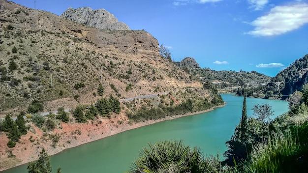 昼間に山の横を流れる川の広角ショット 無料写真