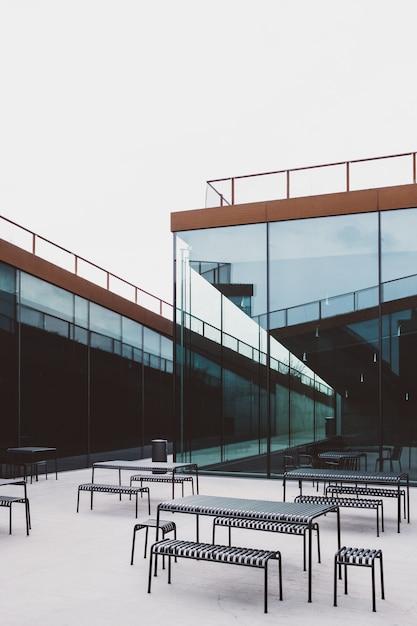 유리 건물 앞에 놓인 여러 테이블의 와이드 앵글 샷 무료 사진