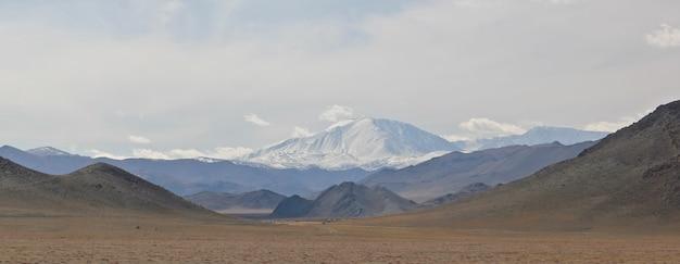 曇った空の下の山々の広角ショット 無料写真