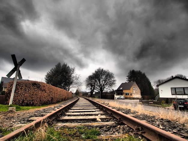 Wide angle shot of the railway tracks surrounded by trees under a clouded sky Free Photo