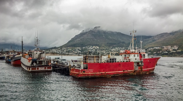 Wide angle shot of several ships on the water behind the mountain under a cloudy sky Free Photo