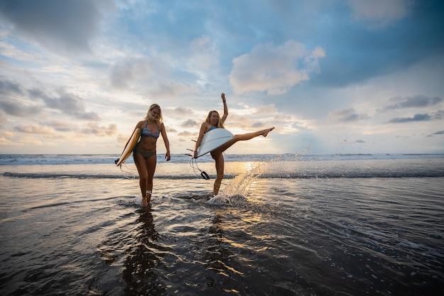 Colpo grandangolare di due donne in piedi sulla spiaggia durante un tramonto Foto Gratuite