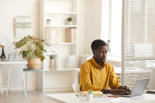 최소한의 사무실 인테리어, 복사 공간에 책상에서 작업하는 동안 노트북을 사용하는 현대 아프리카 계 미국인 남자의 넓은 각도보기 프리미엄 사진