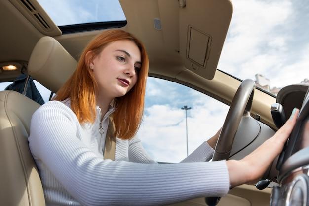 ヒーターを調整する車を運転するシートベルトで固定された若い赤毛の女性ドライバーの広角ビュー。 Premium写真