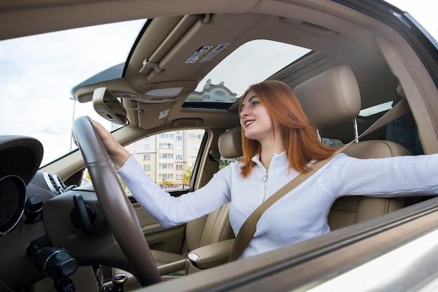 幸せな笑顔で車を運転するシートベルトで固定された若い赤毛の女性ドライバーの広角ビュー。 Premium写真