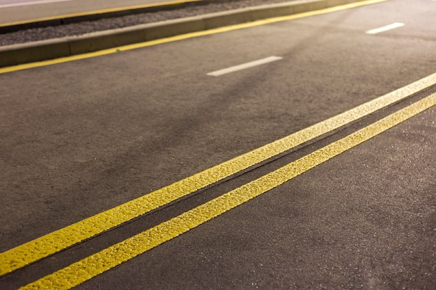 Wide bright double yellow marking sign line along modern wide smooth empty asphalt highway street stretching to horizon. speed, safety, comfortable journey and professional road building concept. Premium Photo