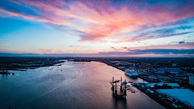Wide distant shot of boats floating on the body of water in the city under a pinkish sky Free Photo