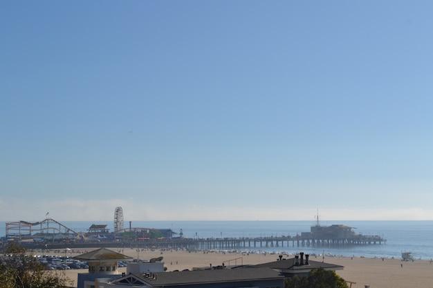 澄んだ青い空の下で海沿いのドックの遊園地の遠く離れたショット 無料写真