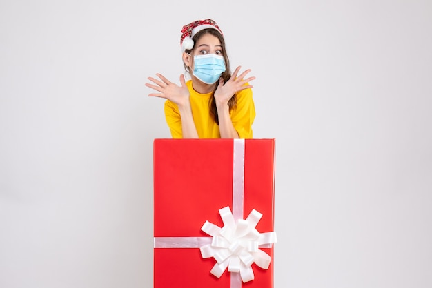 Wide-eyed girl with santa hat opening hands standing behind big xmas gift on white Free Photo