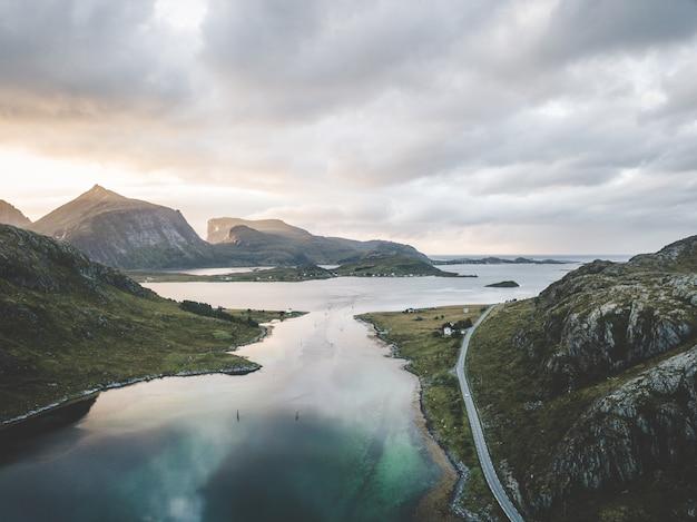 Широкий пейзаж выстрел из моря в окружении гор под розоватым небом с облаками Бесплатные Фотографии