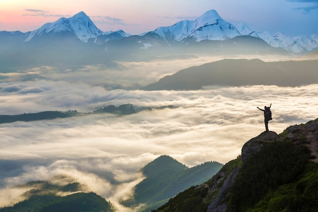 Wide mountain panorama. small silhouette of tourist with backpack on rocky mountain slope with raised hands over valley covered with white puffy clouds. beauty of nature, tourism and traveling concept Premium Photo