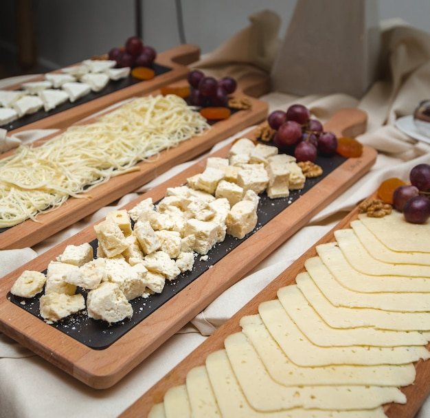 A wide selection of cheese platters with fresh grapes on the table. Free Photo