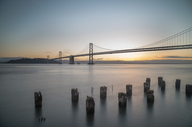 Wide shot of bay bridge on the body of water during sunrise in san francisco, california Free Photo