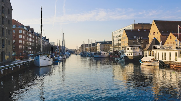 Wide shot of boats on the body of water near buildings in christianshavn, copenhagen, denmark Free Photo