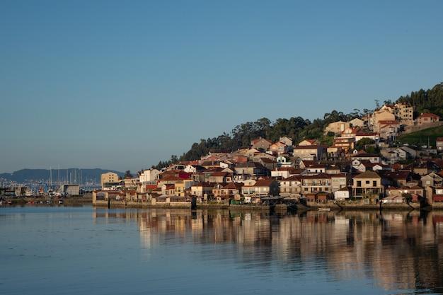 Ripresa a tutto campo di una città piena di case su una collina in riva al mare in una giornata fresca Foto Gratuite