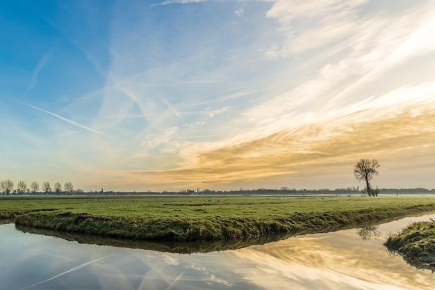 Ripresa a tutto campo di un campo erboso con un corpo d'acqua che riflette il bel tramonto e il cielo Foto Gratuite