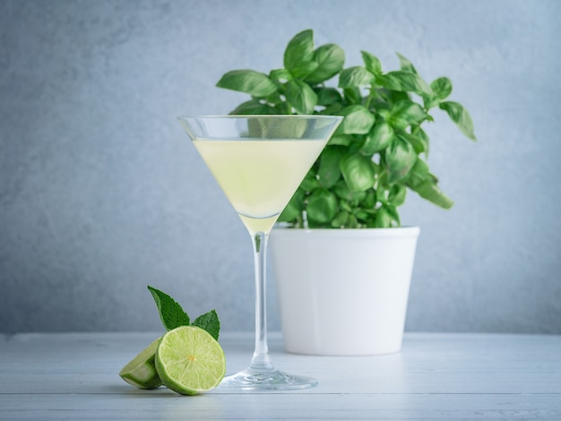 Wide shot of lime martini in a cocktail glass near lime and mint and a basil plant in a white pot Free Photo