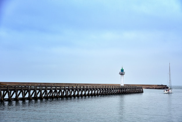Wide shot of a long pier in the sea under the beautiful blue sky Free Photo