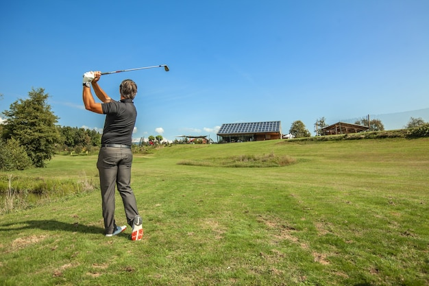 Wide shot of a male athlete swinging a golf club on a sunny day in a golf course Free Photo