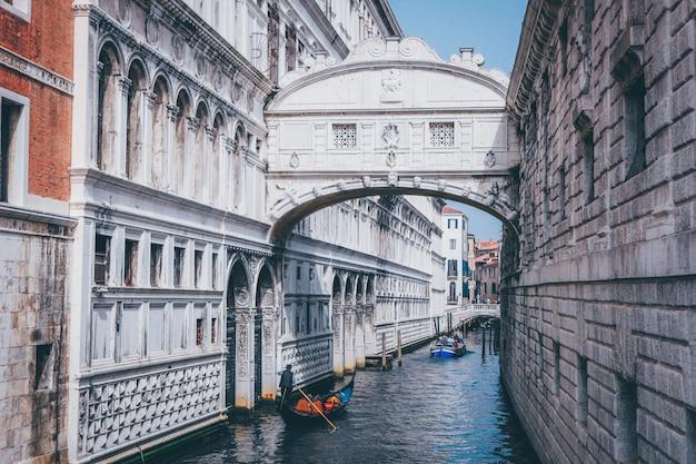 Широкий выстрел человека, гребущего на гондоле на реке под мостом вздохов в венеции, италия Бесплатные Фотографии
