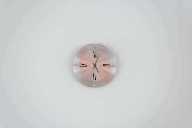白い壁にバラの金の壁時計のワイドショット 無料写真