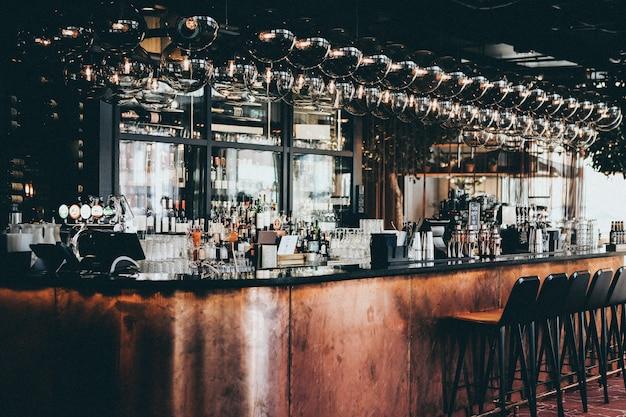 デンマーク、コペンハーゲンのスカンディックホテルのバーにあるディスプレイキャビネットのボトルとグラスのワイドショット 無料写真