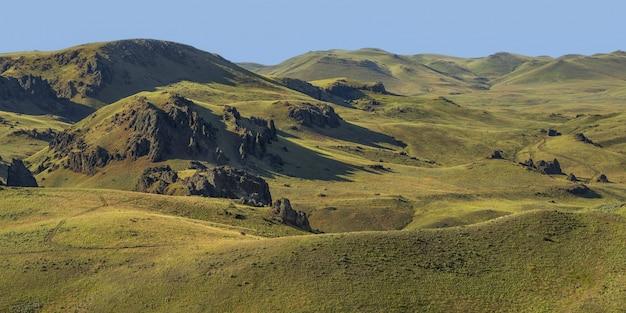 昼間の背景に青い空と空の草が茂った丘のワイドショット 無料写真