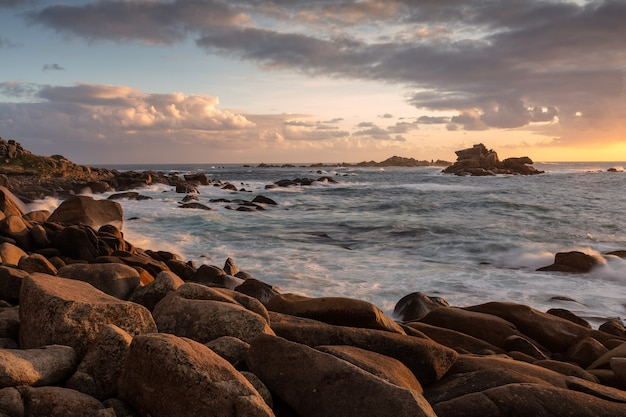 曇り空と日没時に海岸の岩で海のワイドショット 無料写真