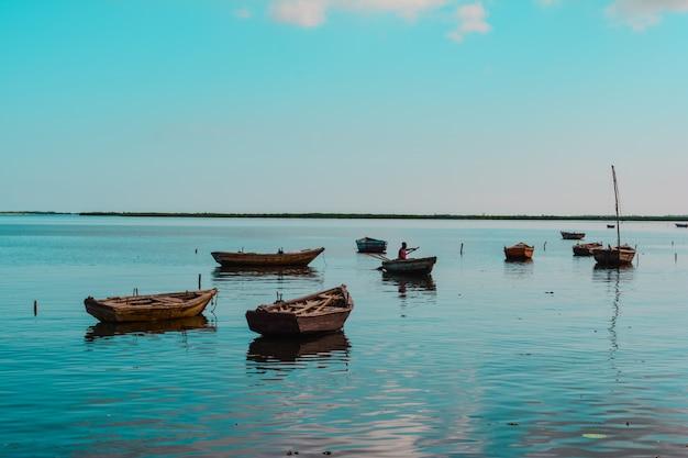 それらの1つでアフリカ系アメリカ人の人と水の中の木製の小さなボートのワイドショット 無料写真