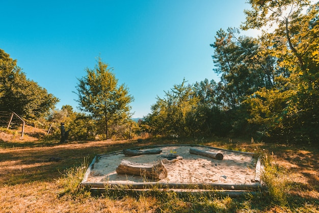 Wide shot of a park with a firepit in a sandbox surrounded by plants and trees Free Photo