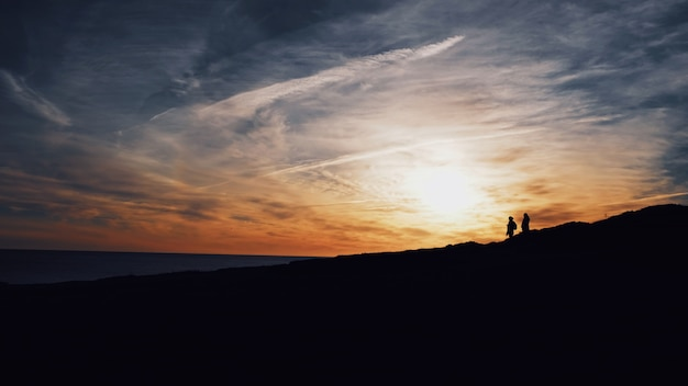 Wide shot of silhouettes of two people walking on a hill with the sun shining Free Photo