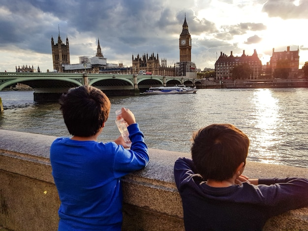Wide shot of two young boys enjoying the view of beautiful architecture from a bridge Free Photo