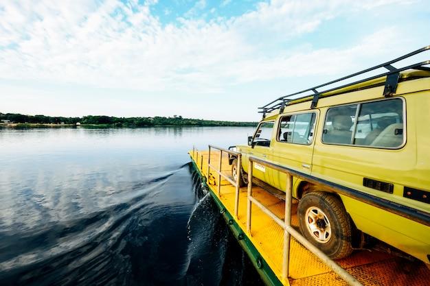 Panoramica di un furgone giallo su un bacino giallo dal mare sotto un chiaro cielo con le nuvole Foto Gratuite