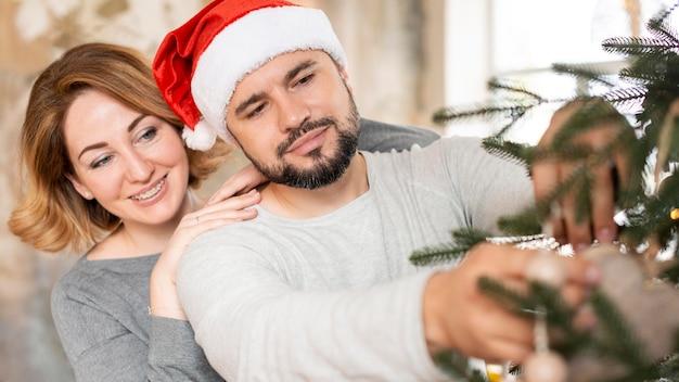 Жена и муж вместе украшают елку Бесплатные Фотографии