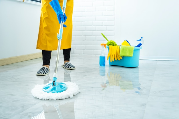 Wife housekeeping and cleaning concept, happy young woman in blue rubber gloves wiping dust using mop while cleaning on floor at home Premium Photo