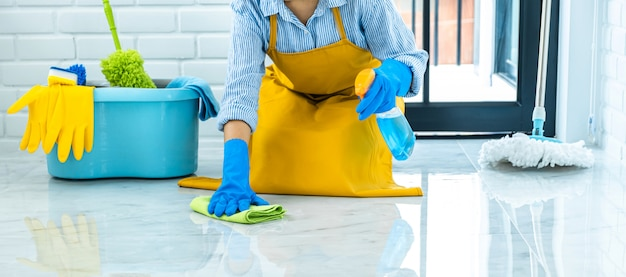 Wife housekeeping and cleaning concept, happy young woman in blue rubber gloves wiping dust using a spray and a duster while cleaning on floor at home Premium Photo
