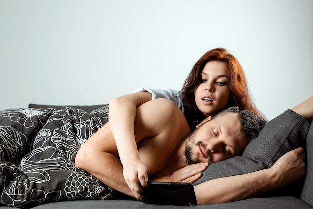The wife is spying on her husband's phone while he sleeps Premium Photo