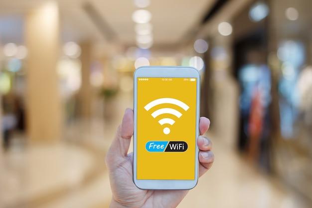 ショッピングモールの背景にぼやけて画面上に無料のwifiとスマートフォンを持っている手 Premium写真