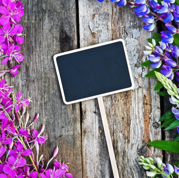 Дикие цветы и черная доска Premium Фотографии