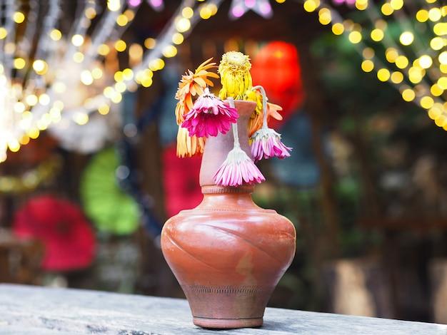 木製のテーブルの上に茶色の花瓶にしおれたガーベラの花 Premium写真