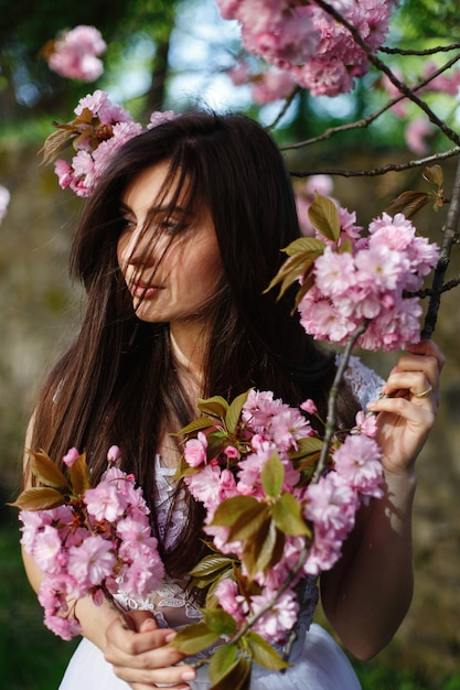 Wind blows brunette woman's hair while she poses before a blooming sakura tree Free Photo