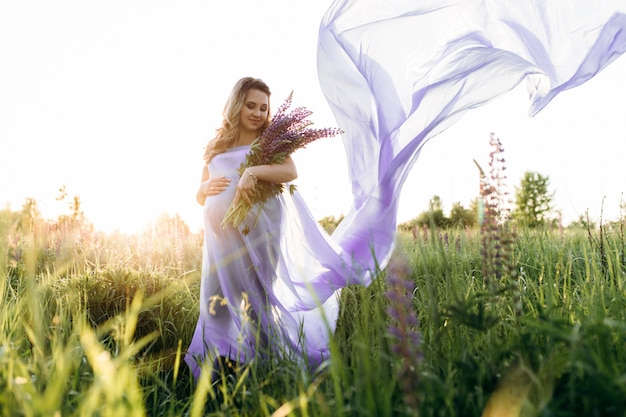 Wind blows pregnant woman's violet dress while she stands in the field of lavender Free Photo
