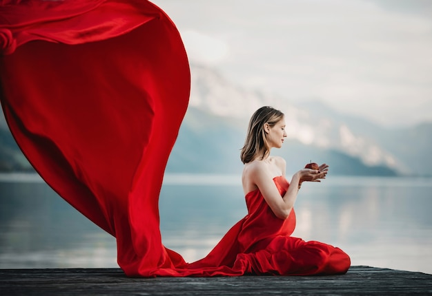 Wind blows red dress of a pregnant woman sitting with apple on the bridge over the lake Free Photo