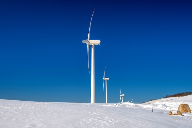 Wind turbine and blue sky in winter landscape Free Photo