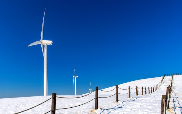 Wind turbine and blue sky in winter landscape Free Photo