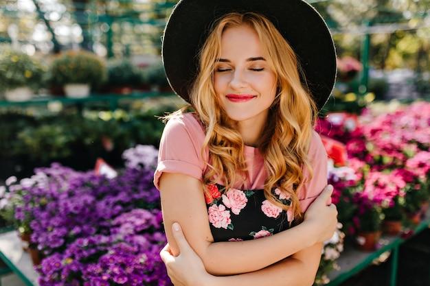 눈으로 웃 고 Winderful 여자 오렌지에 폐쇄. 꽃의 Frint에 서있는 아름 다운 로맨틱 여자. 무료 사진