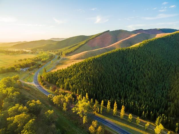 Winding road passing through beautiful australian countryside at sunset Premium Photo