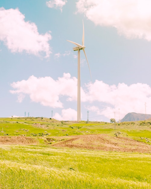 Windmill in green meadow on sunny day Free Photo