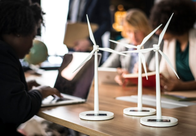 Windmill models on a meeting table Free Photo